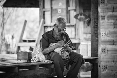 asia life old man uncle grandfather working in home  asia old man living in the countryside of life rural people in thailand  weave bamboo basket crafts
