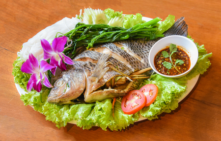 steamed fish on plate / cooking food tilapia fish steamed with chilli sauce spicy and boiled vegetables tomato lettuce orchid on wooden background -  tilapia fish thai style food 免版税图像