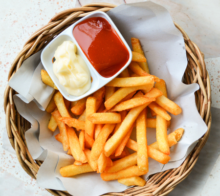 French fries on basket with cream and tomato sauce / Crispy potato fresh french fries ketchup sauce for snack on top view 写真素材
