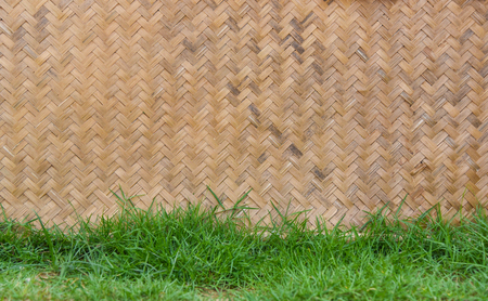 weave pattern and green geass on ground / weave texture from nature bamboo wicker traditional weave pattern handicraft thai style vintage background Stock Photo