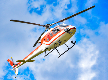 helicopter flying on sky / white red fly helicopter on blue sky with clouds good air bright day  - helicopter rescue