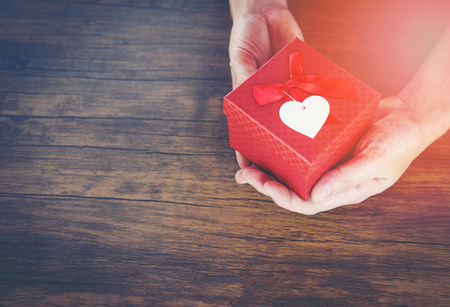 Give Love Man holding small red present box in hands with Heart for love Valentines day concept / Giving a gift box with red ribbon in hand man on wooden background