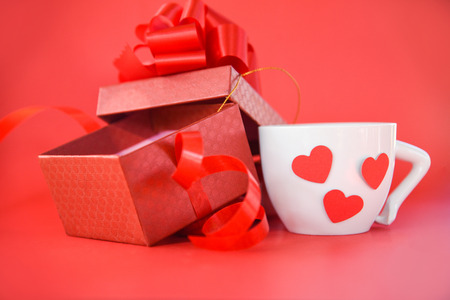 Open Gift Box and white Coffee cup with red heart  present box with ribbon bow for gift to Merry Christmas Holiday Happy new year or Valentines day on red background Stock Photo