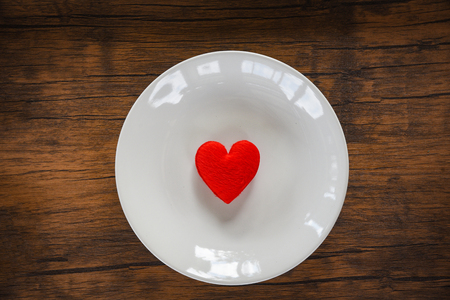 Valentines dinner romantic love food and love cooking concept  Red heart on white plate romantic table setting decorated with red heart wooden rustic texture background