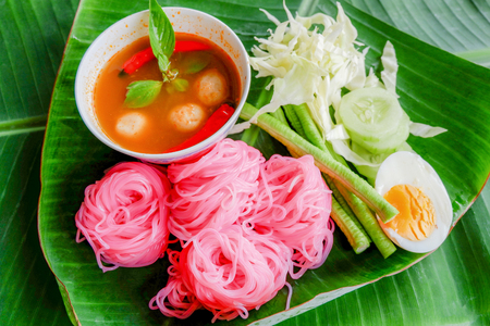 rice noodle colorful pink or rice vermicelli noodle and fish curry soup sauce with vegetable on plate banana leaf background / Thai style food delicious and beautiful foodbeautiful food Stock Photo