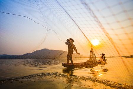 Pêcheur sur le coucher du soleil sur la rivière en bateau / Filet de pêcheur en Asie utilisant sur un bateau en bois le coucher du soleil ou le lever du soleil sur le fleuve Mékong - Bateau de pêcheur silhouette avec fond de montagne campagne personne vie