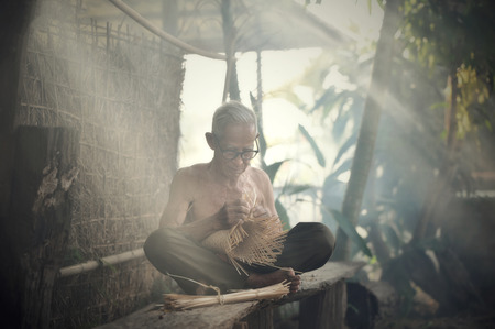 Asia life old man uncle grandfather working in home / asia old man elderly serious living in the countryside of life rural people in thailand / weave bamboo basket crafts