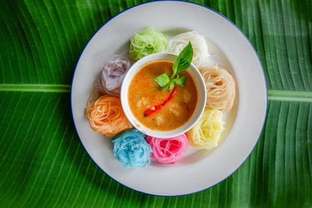 Food thai noodle vermicelli / colorful rice noodle vermicelli curry soup sauce on white plate on banana leaf background / Thai style food delicious and beautiful