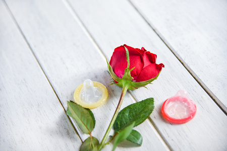Condom Prevent Pregnancy Contraception Valentines safe concept / Birth Control with Condom and roses flower love on white wooden background - pregnancy or sexually transmitted disease