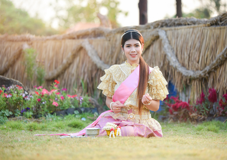 Asia woman thai style dress / Portrait of beautiful young girl smiling Thailand traditional costume wearing with thai jasmine garland in hand