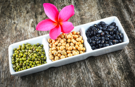 whole grains seeds various lentils with mung bean , black bean and soybean cereal mix in white cup with frangipani flower plumeria on wood background