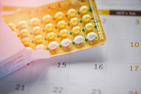Oral Contraceptive pill Prevent Pregnancy Contraception concept / Birth Control with calendar background - health care and medicine