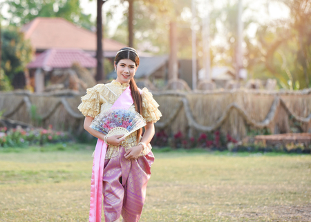 Asia woman thai style dress / Portrait of beautiful young girl smiling Thailand traditional costume wearing with paper fan in hand