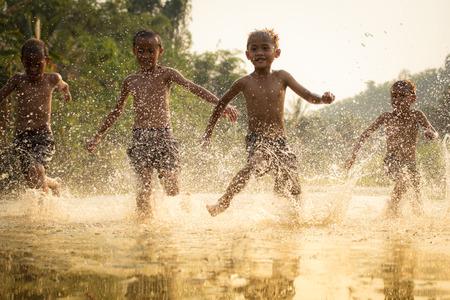 Los niños de Asia en el río / El novio feliz divertido jugando corriendo en el agua en el campo de la vida de los niños campesinos campesinos Foto de archivo
