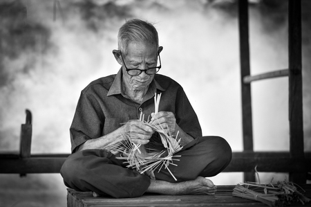 Asia life old man uncle grandfather working in home  Man elderly serious living in the countryside of life rural people in thailand weave bamboo basket crafts
