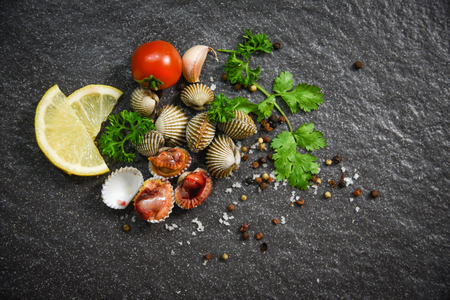 Shellfish Seafood Cockles fresh raw ocean gourmet dinner with herbs and spices on dark background - blood cockle peeled