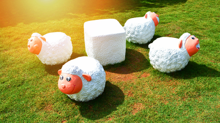 Group of cute white sheep statue on grass in the garden park for bench