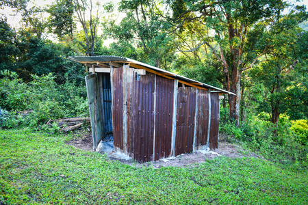 Old wooden toilet forest with zinc roof on mountains in a village hill - Outhouse toilet cabins