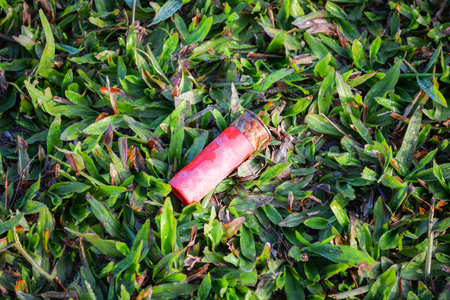 Old red shotgun Shelling gun that has been fired on green grass - Firearms ammunition cartridges