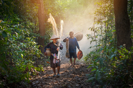Asia fisherman hold net and fishing tools walking in the forest to river life person countryside
