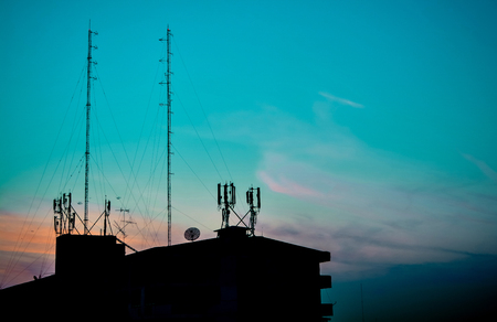 Silhouette of buildings at sunset view house and communication radio tower on blue sky blackground