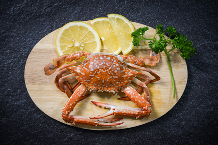 Crab cooked shellfish seafood on cutting board with herbs and spices on dark background  Steamed Blue Swimming Crab