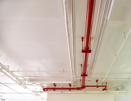 Red water pipe fire equipment / Metal water piping system install with the concrete under building Foto de archivo - 118852319