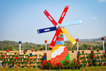 Colorful windmill wind turbine in the garden with strawberry plant and flower in pot on view hill background