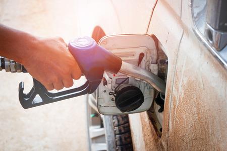 Handle fuel nozzle to refuel in gas station Standard-Bild - 118853099