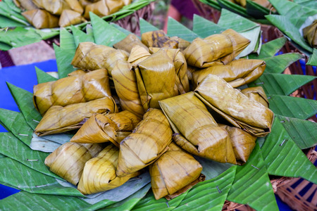 Thai dessert wrapped with banana leaf cooked made from sticky rice , bean and banana after steam