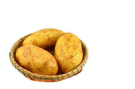Fresh organic potato in basket isolated on white background Фото со стока