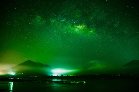 Milky Way galaxy landscape rivers on green color and light with mountains background on the dark sky night in thailand 免版税图像