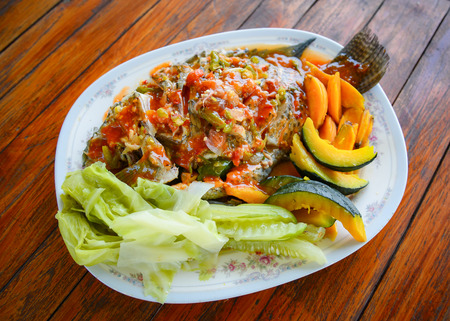 Cooking food tilapia fish steamed herb with chilli sauce spicy topped pumpkin cucumber and vegetables on plate wooden background Foto de archivo
