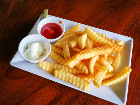 French fries on plate with cream and tomato sauce / Crispy potato french fries ketchup for snack