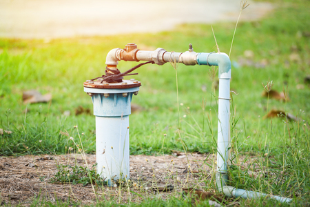 Groundwater well with pvc pipe and system electric deep well submersible pump water on green meadow Stockfoto - 119232187