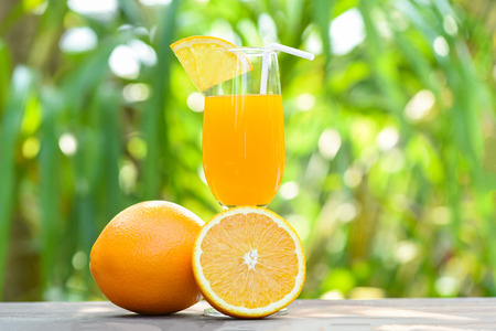 Orange juice with piece orange fruit on glass with nature green summer background - selective focus