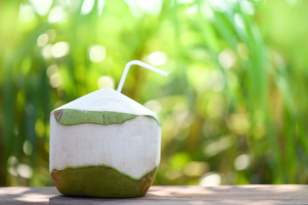 Beverage fresh coconut juice drinking / Young coconut fruit on summer nature green background