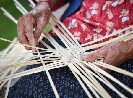 Old senior woman hand working crafts weaving bamboo making basket for nature product in Thailand Asia