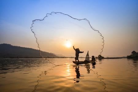 Red de pescadores de Asia con red de lanzamiento de barcos de madera al atardecer o al amanecer en el río Mekong / Barco de pescadores de silueta con fondo de montaña, la vida de la gente en el campo Foto de archivo