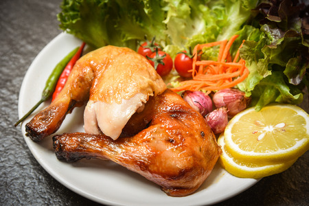 Roasted chicken legs on white plate with lemon chilli spicy herbs spices and salad lettuce vegetable carrot shallottomato on dining table food / Grilled Chicken Stock Photo
