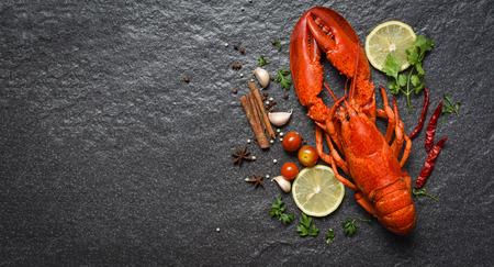 Frutti di mare rossi dell'aragosta con le erbe e le spezie del limone sullo spazio della copia di vista superiore del backgroud scuro