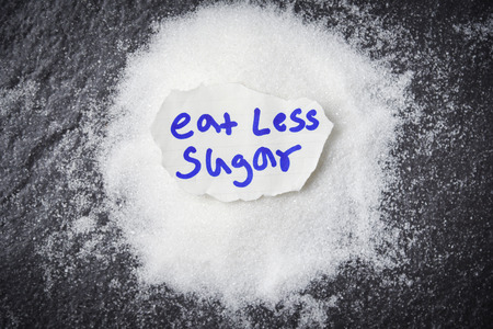 eat less sugar for health concept / Heap of white sugar on dark background