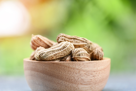 Peanut in wooden bowl and nature green background / Boiled peanuts