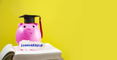 Education concept with pink piggy bank saving money and graduation cap on the open book for scholarships education on yellow background - copy space Foto de archivo