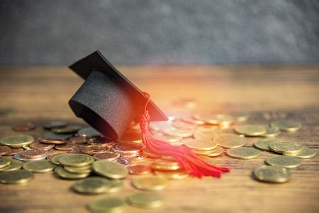 Beca para el concepto de educación con gorro de graduación en la mesa de madera de monedas de dinero Foto de archivo
