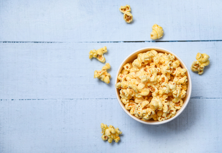 Popcorn in cup bowl and blue wooden  backgroubd top view / Sweet butter popcorn salt 免版税图像