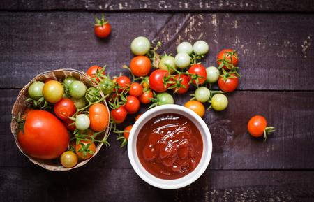 Cosecha orgánica de tomates frescos en la canasta y salsa de tomate en taza de salsa de tomate sobre fondo oscuro de madera - vista superior Foto de archivo