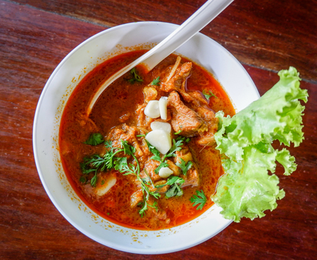 Curry soup pork bone with coconut milk and herbal spices spicy in bowl on wooden background Reklamní fotografie