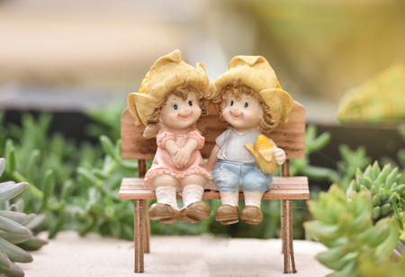 Little couple doll cute sitting on wooden bench decorate the garden backyard with succulent plant background Zdjęcie Seryjne