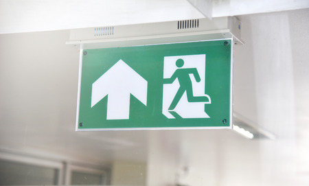 fire exit sign emergency green on wall corporate office building